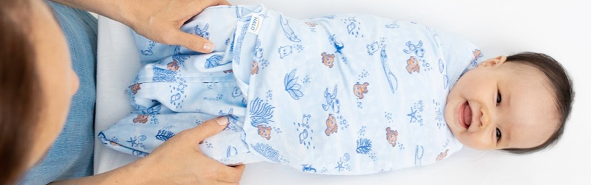 baby on changing table in finding nemo disney tie-dye swaddle by halo