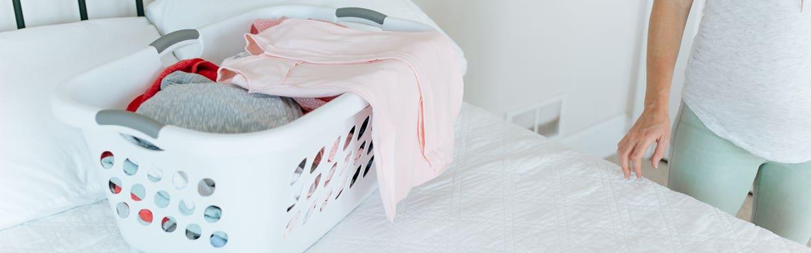 mom putting halo sleepsack swaddle in laundry basket