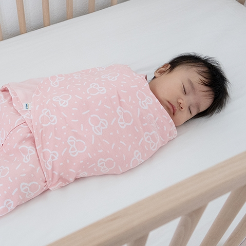 baby sleeping in halo disney sleepsack swaddle in minnie mouse pink print