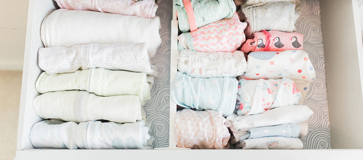 baby clothes organized in a drawer