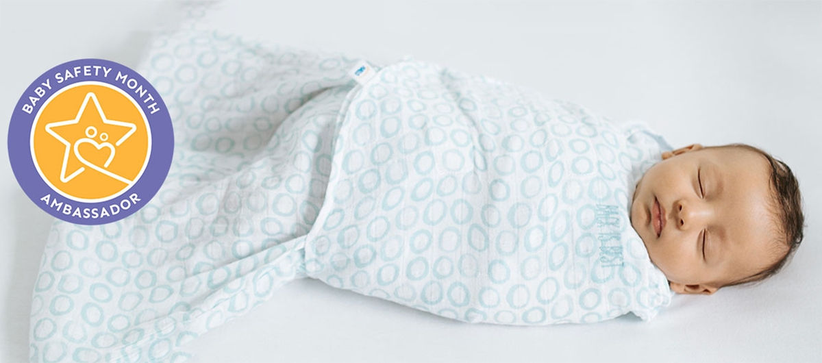 baby sleeping in halo sleepsack swaddle with baby safety month ambassador badge over image