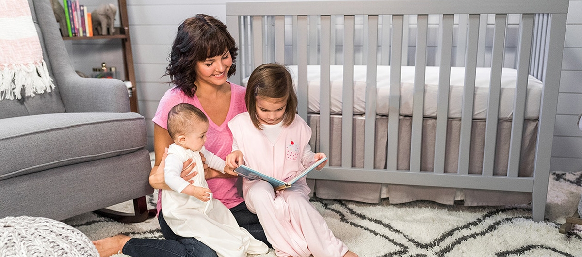 mom reading to toddler and baby in front of crib