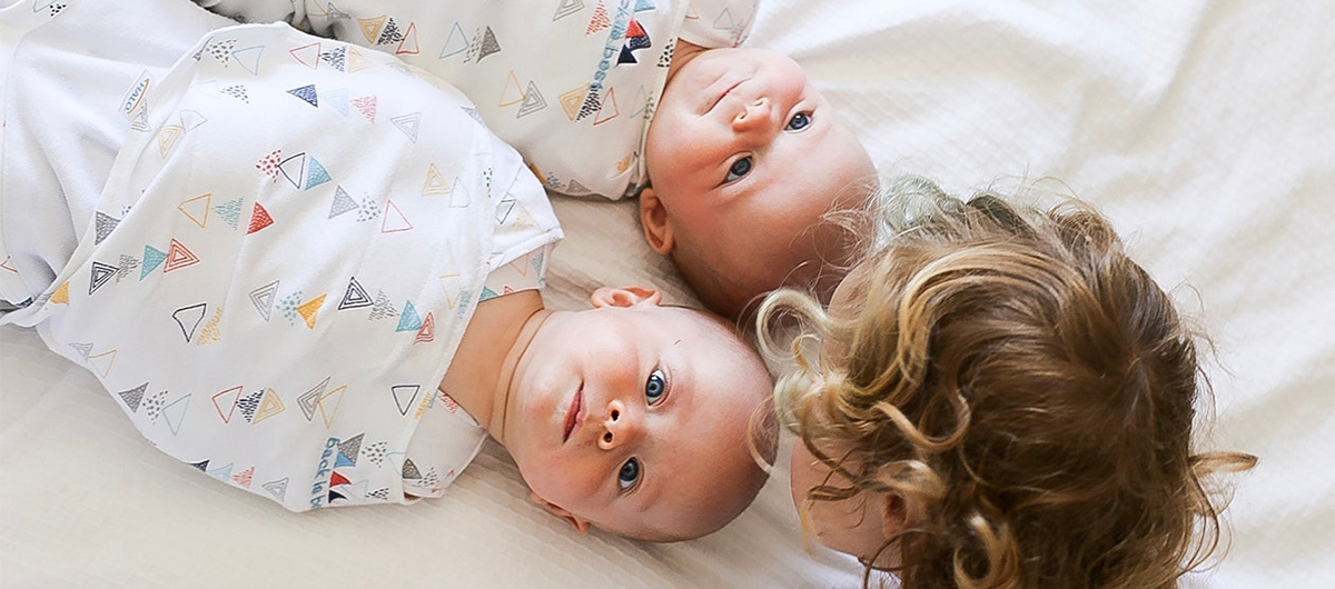 older sibling looking at twins babies laying on bed