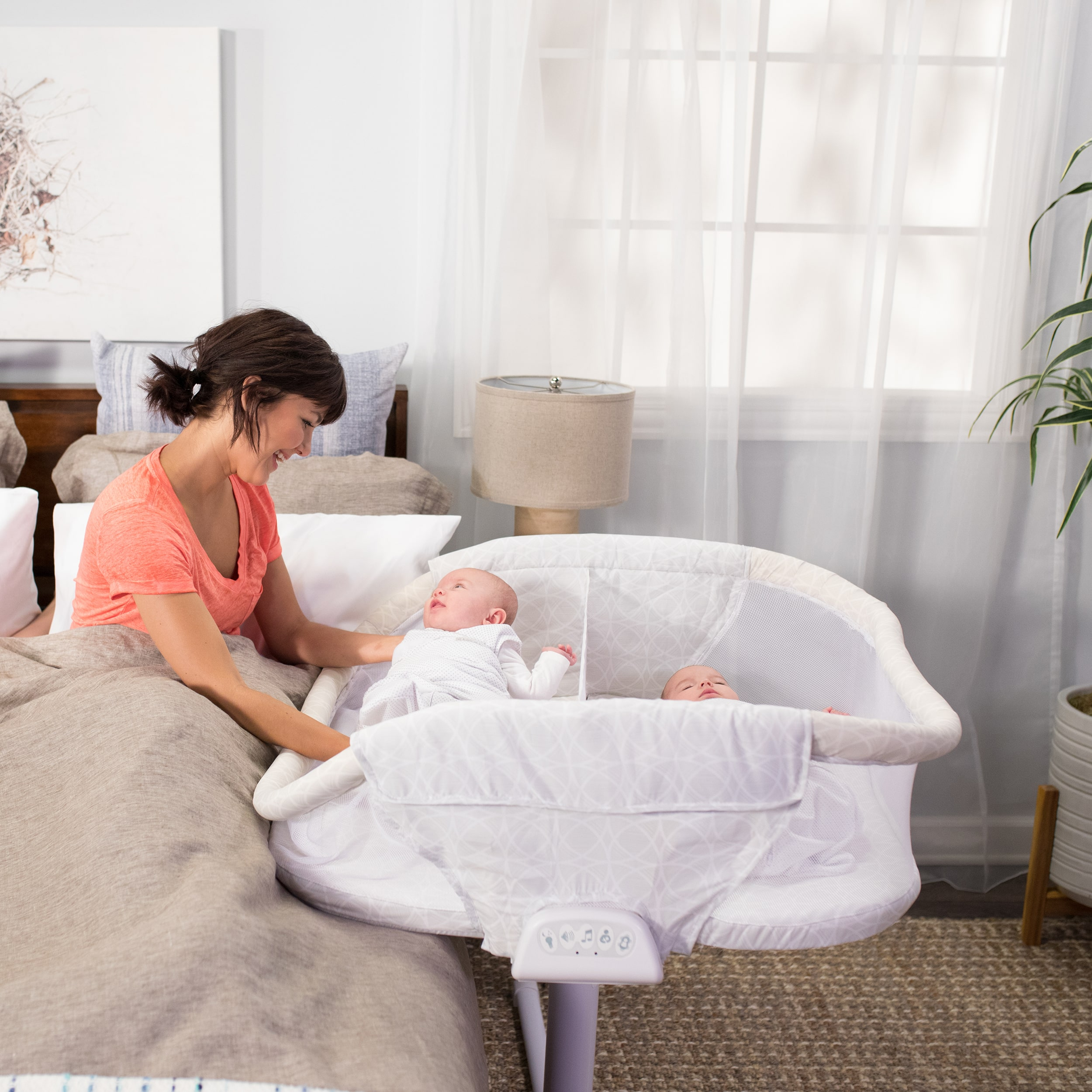 parent using patented lowering bedside wall to take one twin out of the halo bassinest twin sleeper