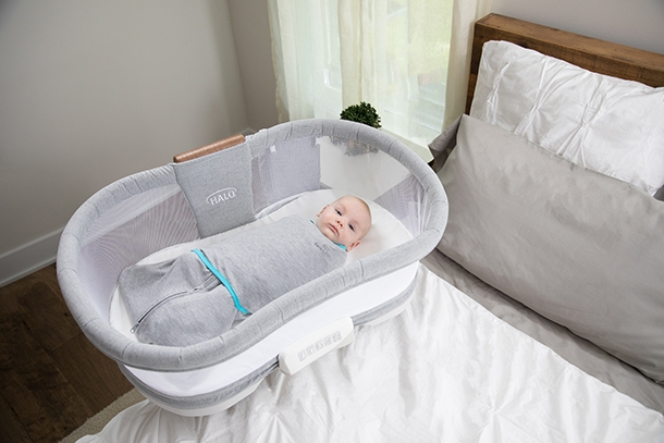 baby resting in bedside bassinet wrapped in temperature regulating swaddle