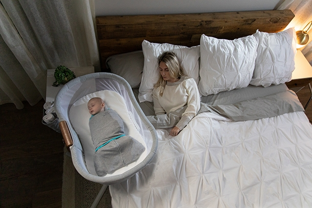 parents sleeping in bed with baby sleeping a bedside bassinet wrapped in tech fabric swaddle