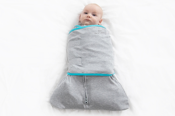 overhead of baby wrapped in tech fabric swaddle