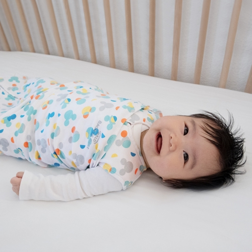baby laying in crib in halo dinsey sleepsack swaddle in mickey overlay print
