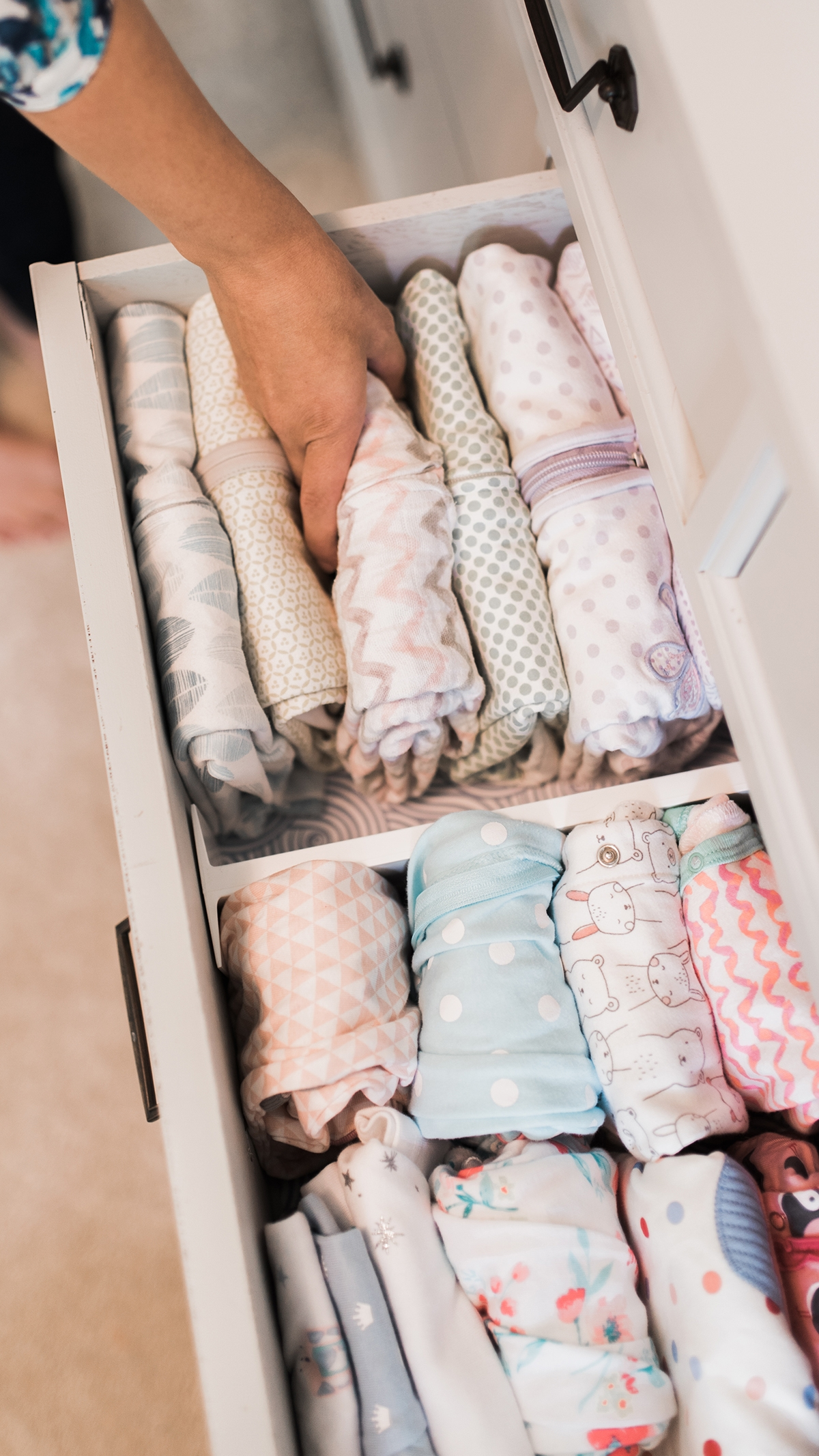 folded halo sleepsacks and other baby clothes organized in drawers