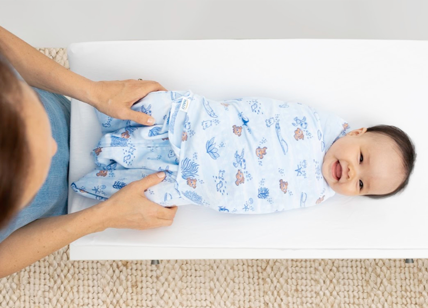baby laying on changing table wrapped in finding nemo tie-dye swaddle
