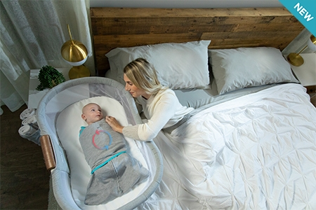 new tech fabric swaddle wrapped around baby in bedside bassinet with mom laying in bed with diagram of temperature regulations