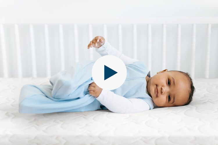 baby laying on side in crib with dreamweave breathable  with play button for video popup