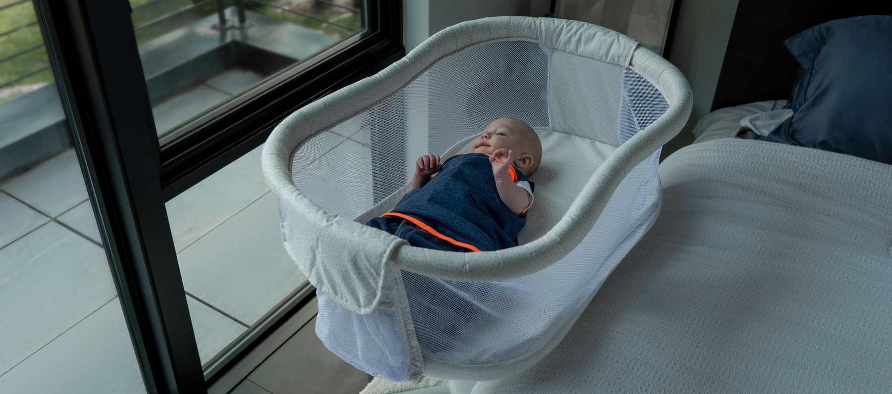 baby laying in bedside bassinet wrapped in navy blue ideal temp temperature regulating swaddle