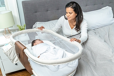 baby sleeping in bedside bassinet with mom in bed
