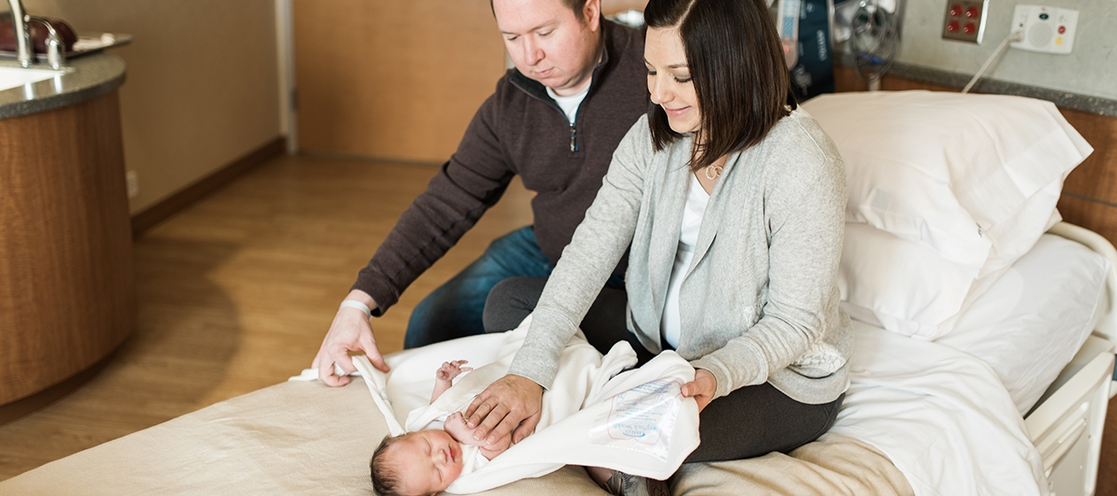 parents sitting on hospital bed wrapping newborn in halo sleepsack swaddle
