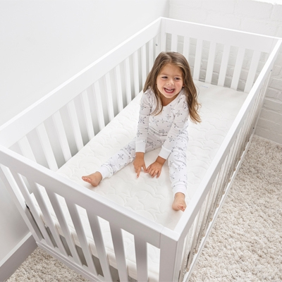 baby in crib with breathable crib mattress for safe sleep