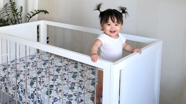 baby stangin in crib with mattress covered in aden and anais essential cribe sheet