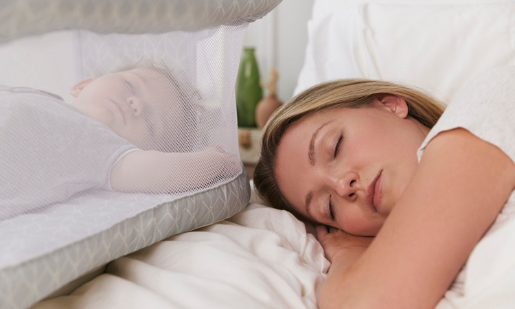 mom laying in bed with baby in bedside bassinest