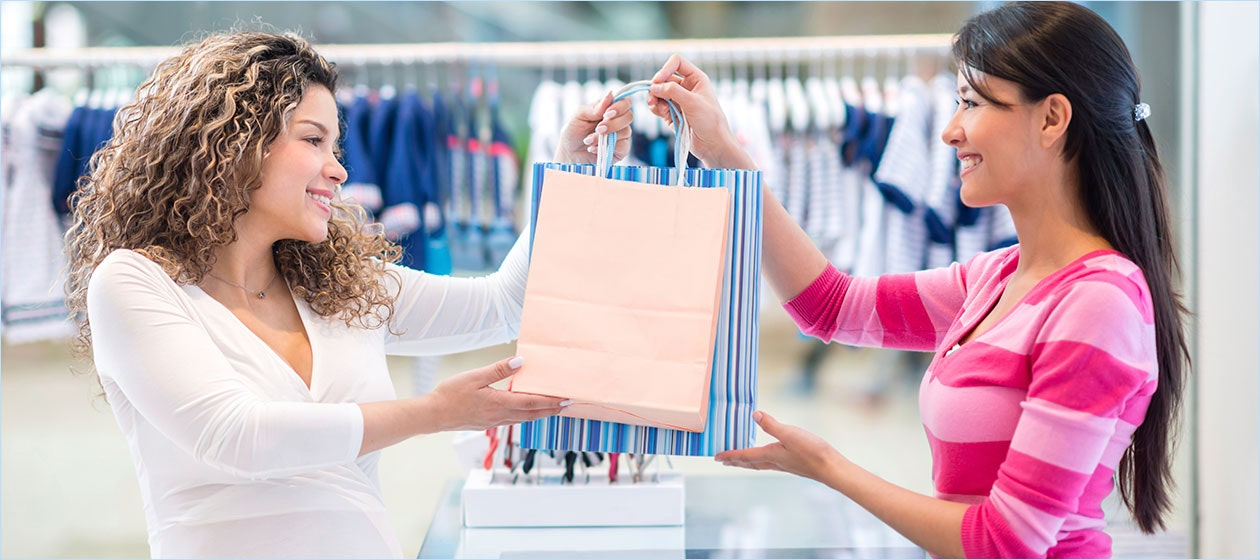 sales associate handing buyer bags