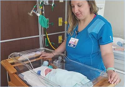 nurse looking after baby in NICU