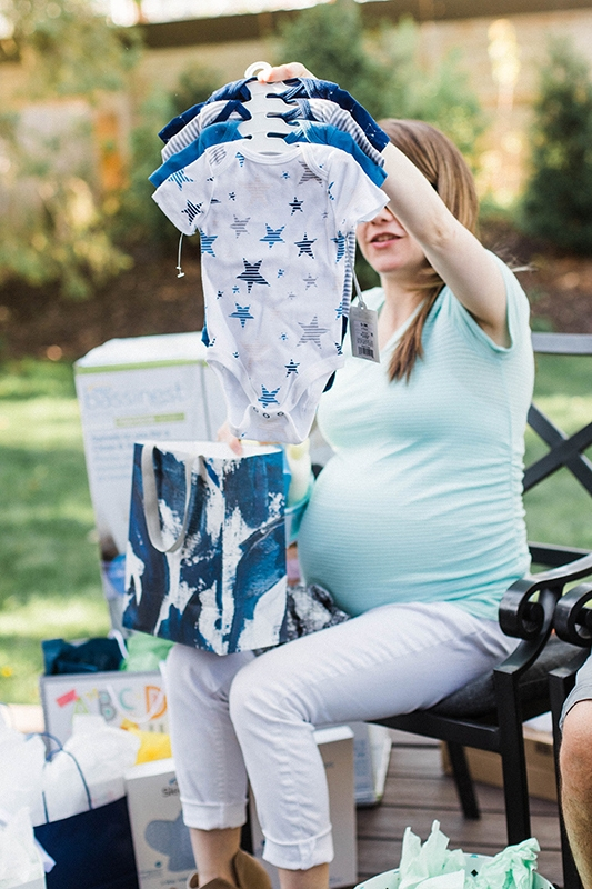 pregnant woman opening baby sprinkle gifts