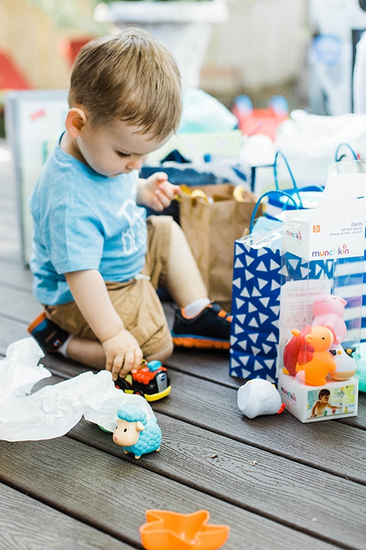toddler playing with toys and surrounded by gifts