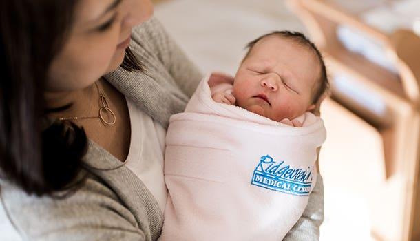 mom holding baby in hospital halo sleepsack swaddle