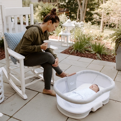 mom sitting outside with cup of coffee with baby on the ground in luxe removable bed