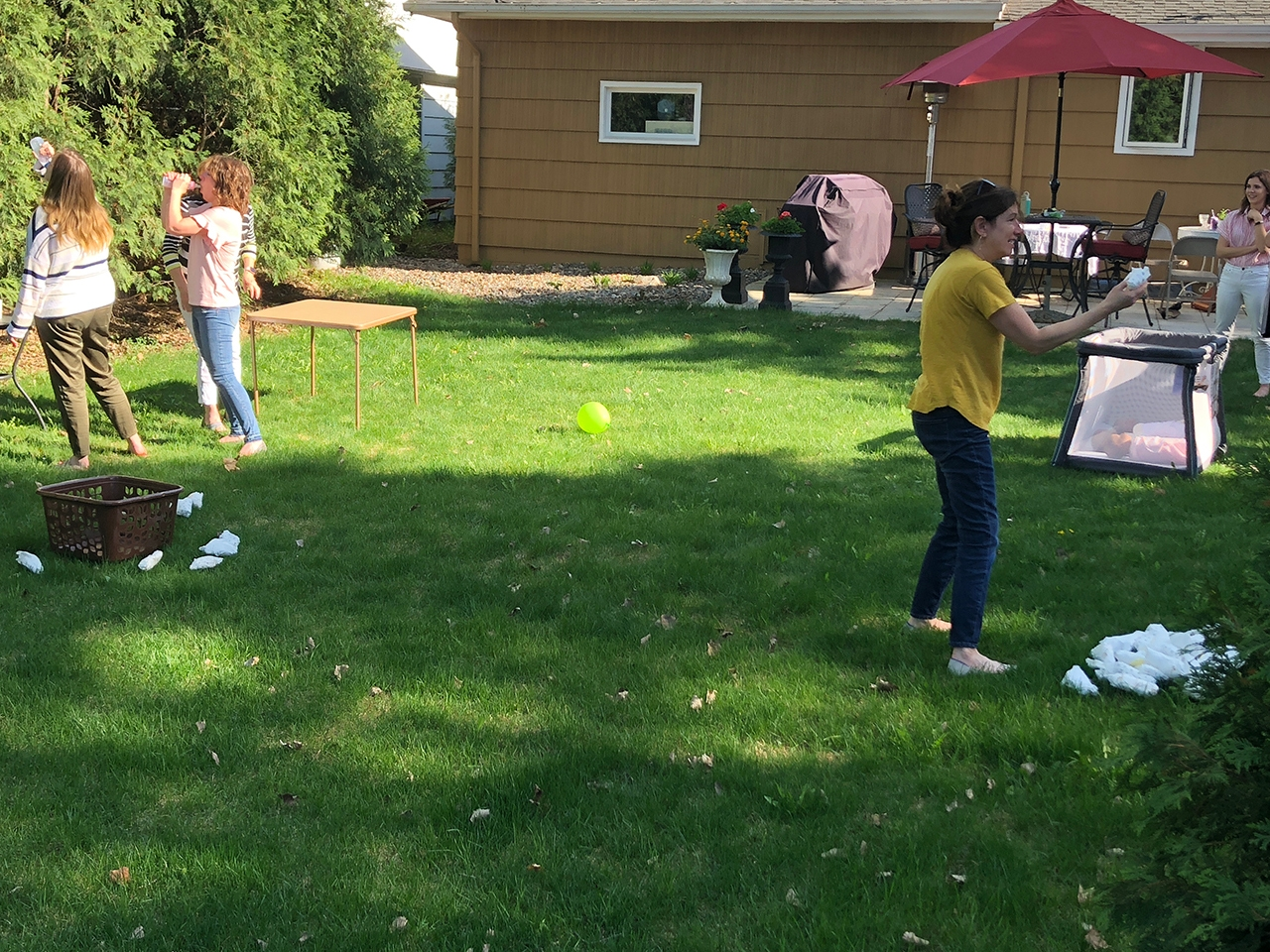 people in backyard playing baby shower games