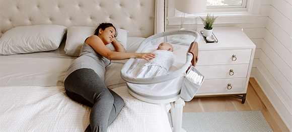 parent laying in bed while baby sleeps in bedside bassinet