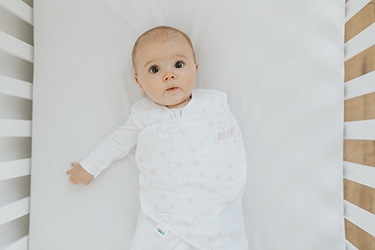 baby laying in crib in swaddle