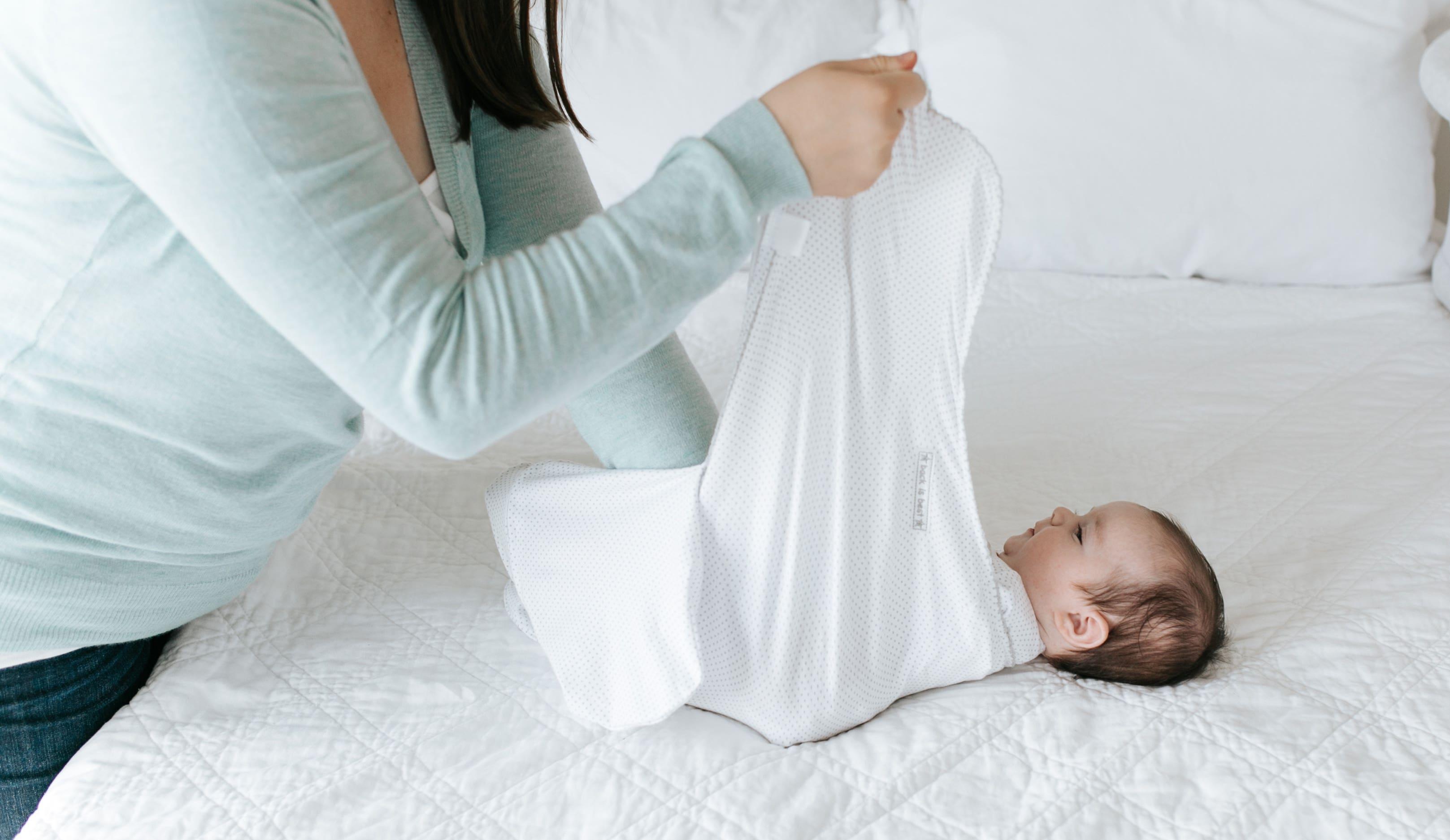 parent wrapping halo sleepsack swaddle around baby