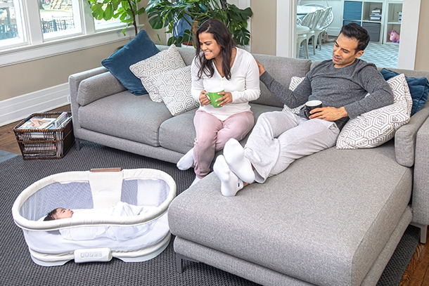 parents sitting on couch with removeable bassinet bed now placed on floor