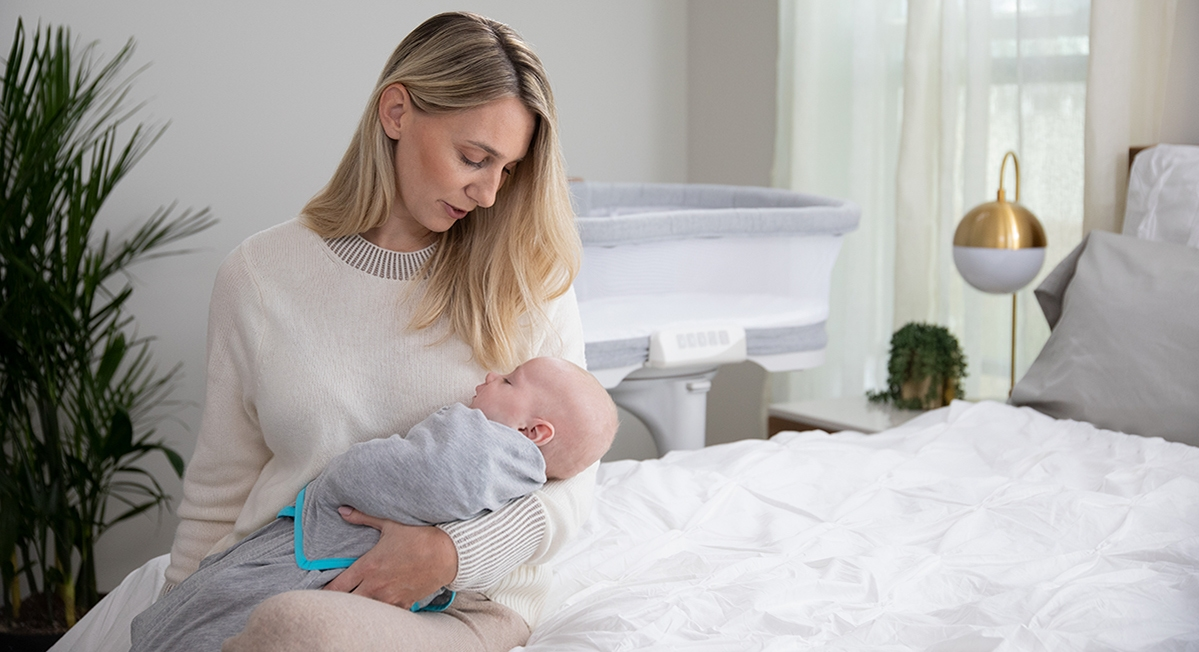 mom holdiing baby wrapped in tech fabric swaddle with a halo bedside bassinet in the background