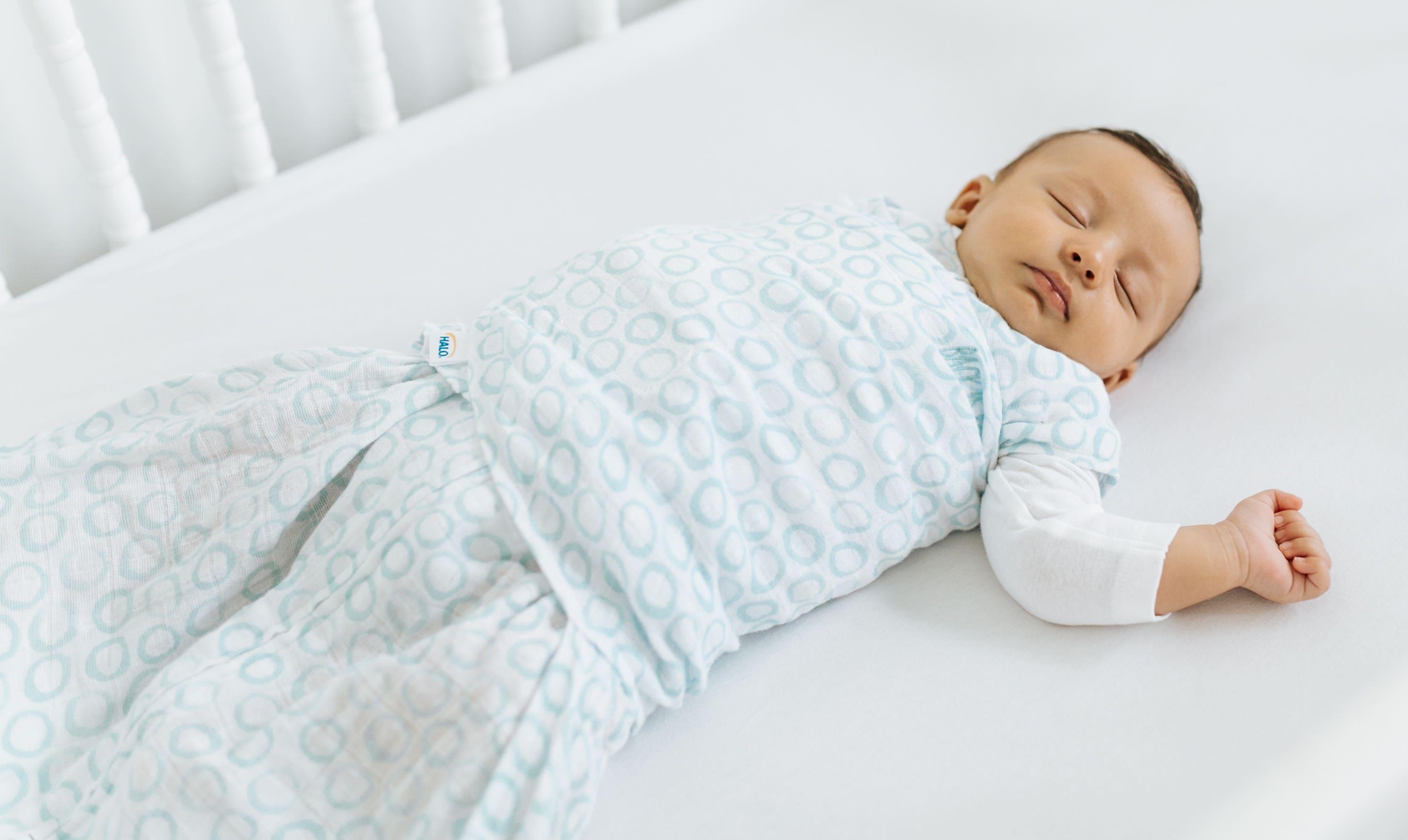 baby sleeping with one arm outside halo sleepsack swaddle