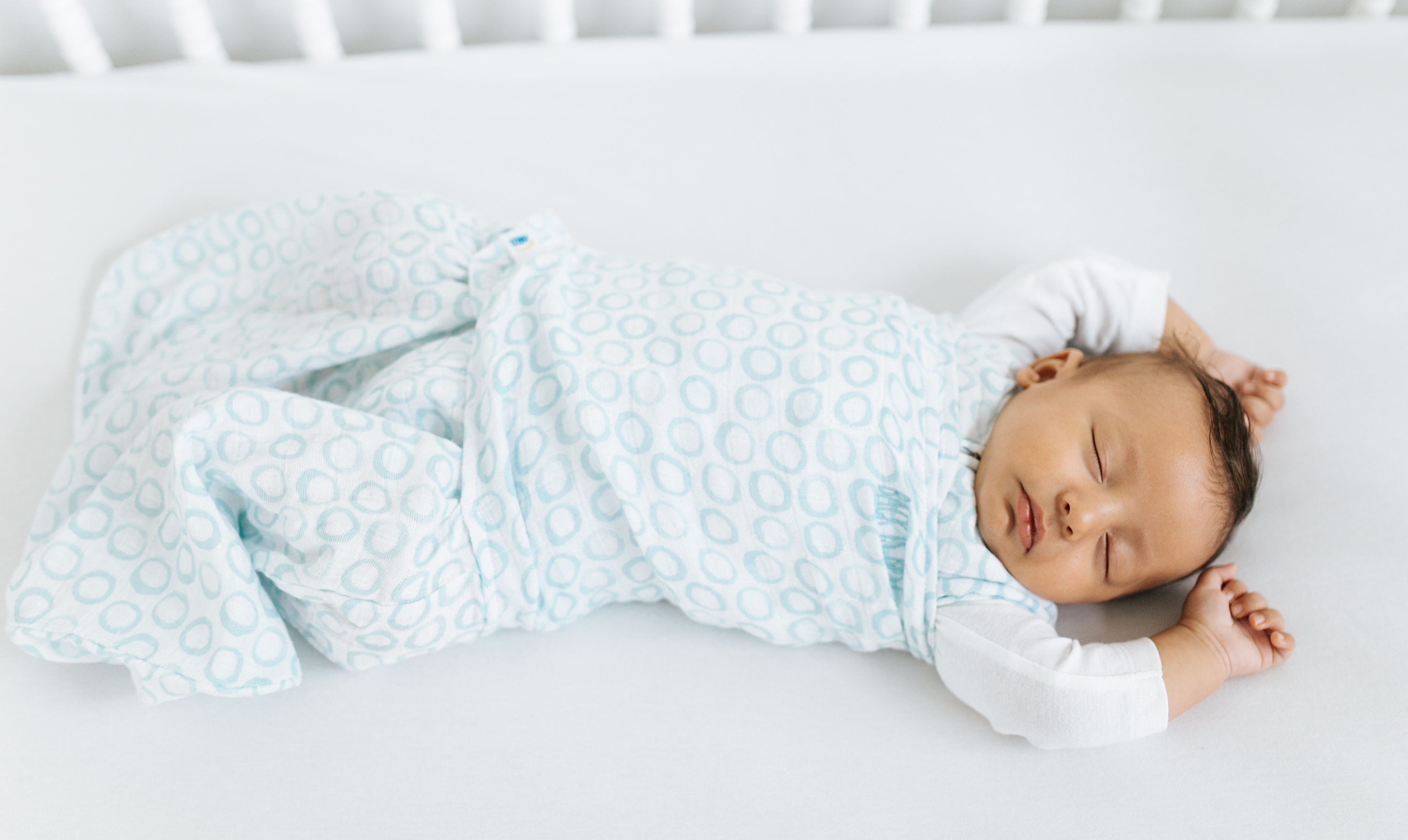 baby sleeping with arms unwrapped from halo sleepsack swaddle