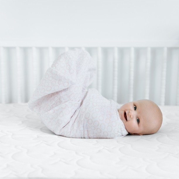 baby laying on breathable crib mattress in halo swaddle